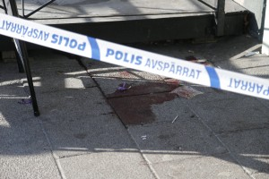 Bloodstain is seen behind police barrier tape at the scene of a fatal shooting in Gothenburg