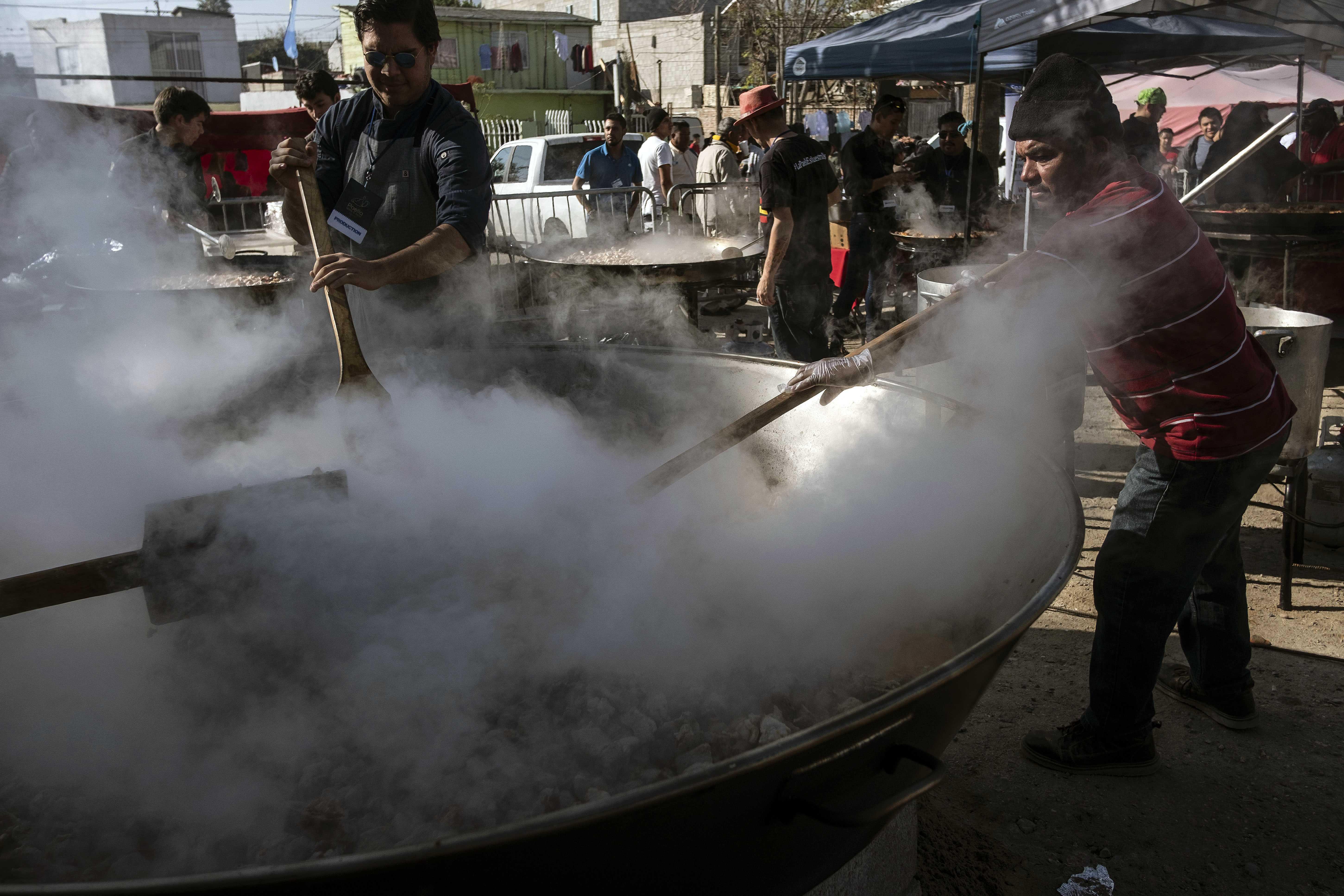 Chefs internacionales cocinan paella para miles de migrantes en Tijuana
