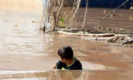 Niños hondureños víctimas de huracanes se bañan en aguas estancadas